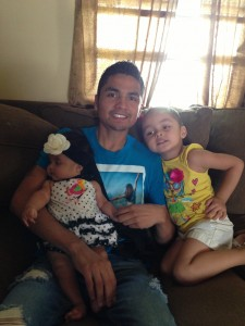 Juan and his daughters on the couch. He needs to be home with them.